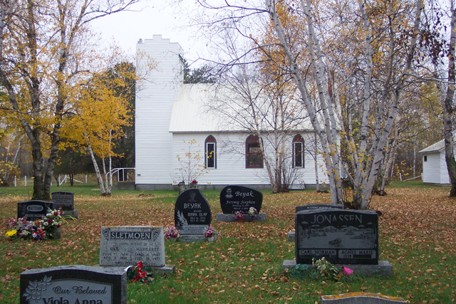 McInnes Creek Chapel / Church with some gravestones in the fore front.: McInnes Creek Chapel / Church has some gravestones with incredible images engraved on them to commererate and provide a tribute to the lives of the people buried there.